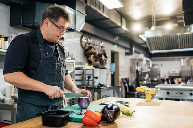 Zijaanzicht van mannelijke chef-kok snijden groenten in de keuken