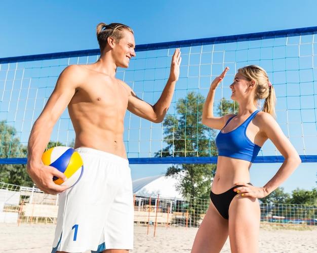 Zijaanzicht van mannelijke en vrouwelijke volleyballers die elkaar high-fiving