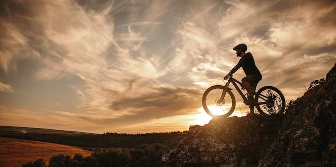 zijaanzicht van mannelijke fietser in helm zittend op de mountainbike tegen bewolkte avondrood op het platteland