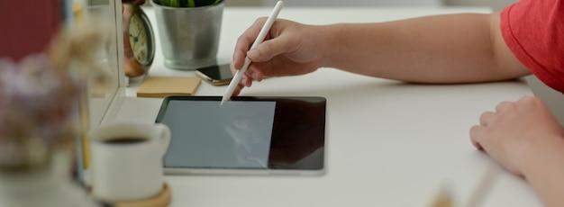 Zijaanzicht van mannelijke freelancer werken op digitale tablet met stylus pen op witte werktafel