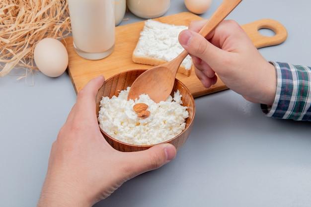 Zijaanzicht van mannelijke handen met kom kwark en houten lepel met sneetje brood besmeurd met kwark melk op snijplank en eieren stro op blauwe oppervlak