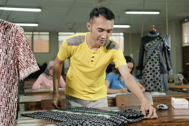 Zijaanzicht van mannelijke kleermaker meet kleding met een liniaal volgens de regels in de kamer