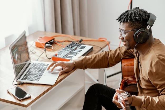 Zijaanzicht van mannelijke musicus die thuis gitaar speelt en met laptop mengt