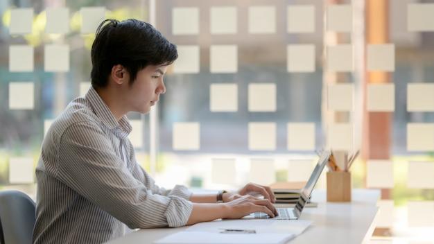 Zijaanzicht van mannelijke ondernemers die op laptop computer in het bureau van de glasmuur typen