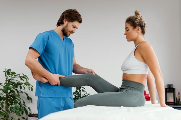 Zijaanzicht van mannelijke osteopathische therapeut die de knie van de vrouwelijke patiënt controleert