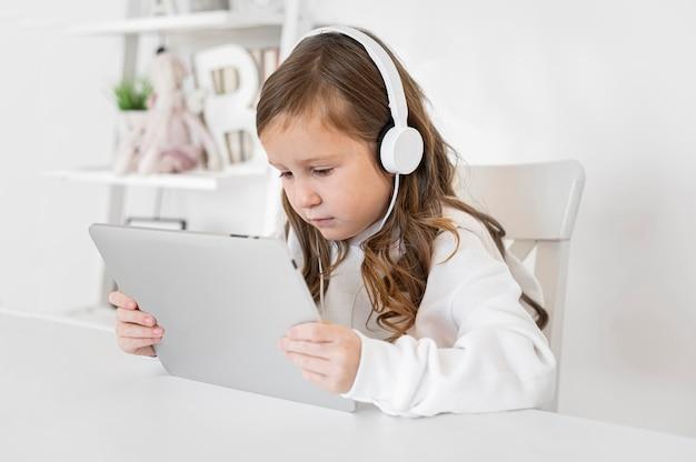 Zijaanzicht van meisje dat tablet met hoofdtelefoons gebruikt
