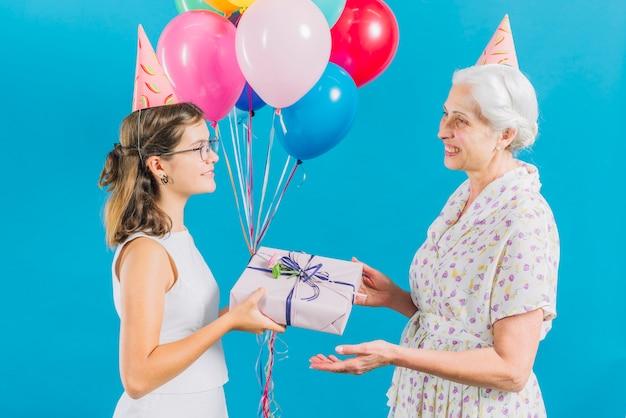 Zijaanzicht van meisje die verjaardagsgift geven aan haar gelukkige grootmoeder op blauwe achtergrond