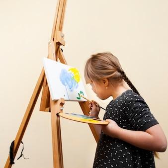 Zijaanzicht van meisje met het syndroom van down schilderen met borstel