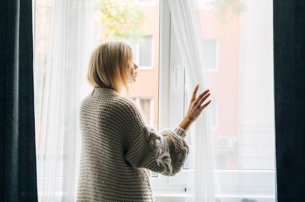 Zijaanzicht van melancholische vrouw thuis tijdens de pandemie die door het raam kijkt