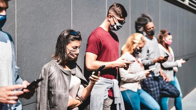 Zijaanzicht van mensen met behulp van mobiele telefoon gedekt door gezichtsmasker - focus op eerste linker vrouw