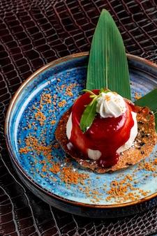 Zijaanzicht van mini cake bedekt met slagroom en aardbeiensiroop en muntblad op een bord op krokodillenleer