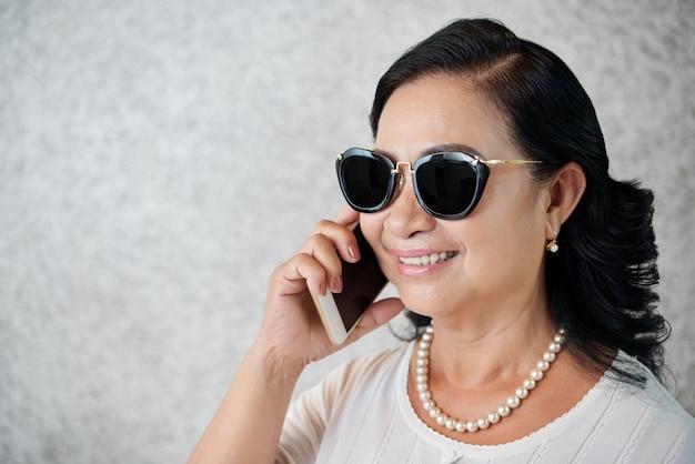 Zijaanzicht van modieuze vrouw van middelbare leeftijd praten aan de telefoon