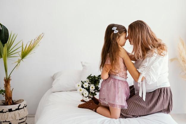 Zijaanzicht van moeder en dochter met boeket van lentebloemen