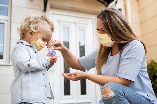 Zijaanzicht van moeder en kind met medische maskers en handdesinfecterend middel