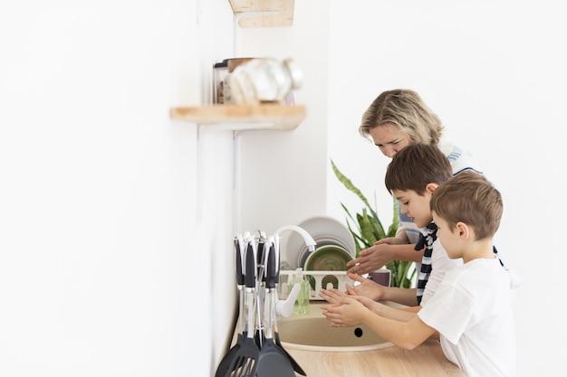Zijaanzicht van moeder en kinderen die hun handen wassen