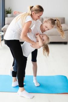 Zijaanzicht van moeder het spelen met dochters thuis terwijl het uitwerken