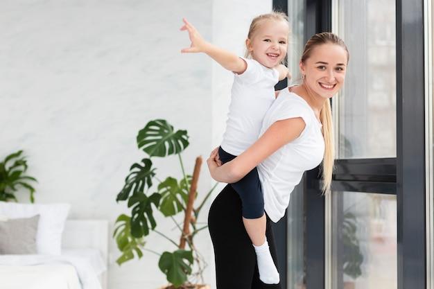 Zijaanzicht van moeder het stellen met dochter thuis terwijl het uitwerken