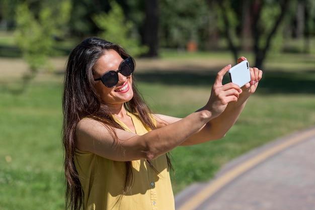 Zijaanzicht van moeder smartphone foto's van haar familie terwijl buitenshuis