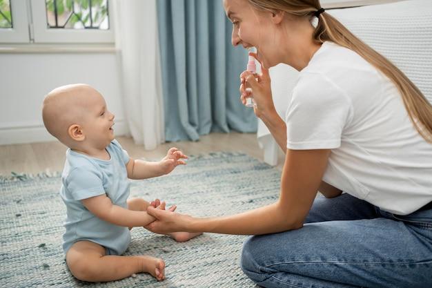 Zijaanzicht van moeder sproeien handdesinfecterend middel op de handen van het kind