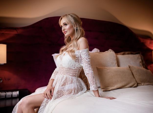 Zijaanzicht van mooie blonde bruid zittend op het bed in een hotelkamer