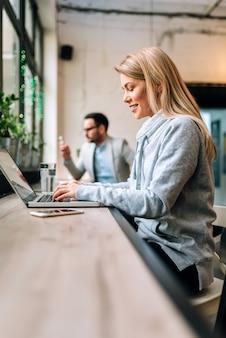 Zijaanzicht van mooie blondevrouw in het toevallige cloting met behulp van laptop bij de koffie.