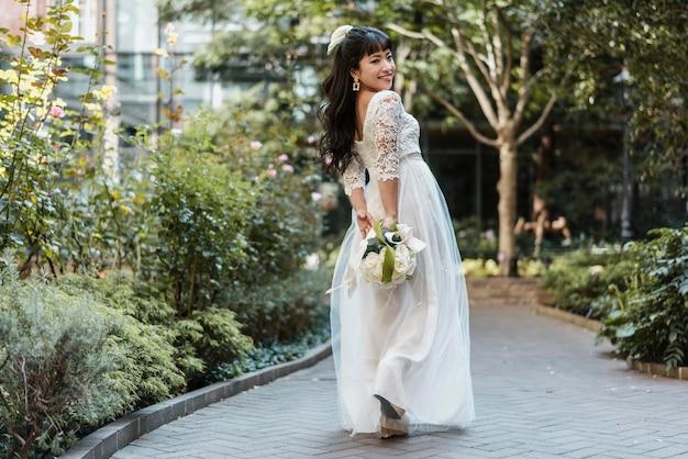 Zijaanzicht van mooie bruid buitenshuis met bloemen