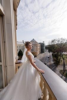Zijaanzicht van mooie bruid die op het balkon staat en geniet van de frisse lucht