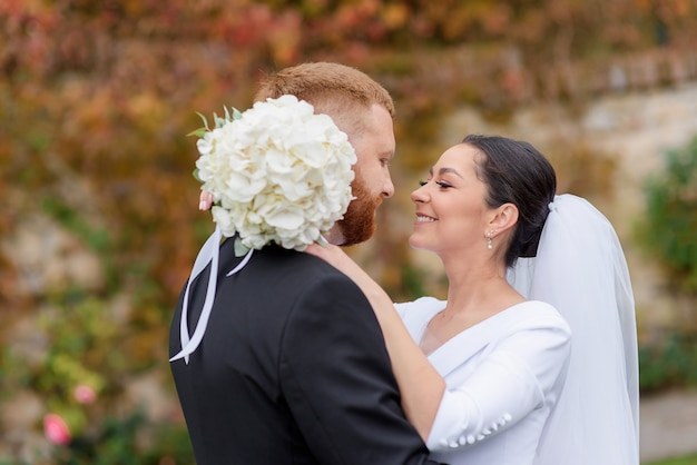 Zijaanzicht van mooie brunette bruid glimlacht en knuffelt haar roodharige bruidegom