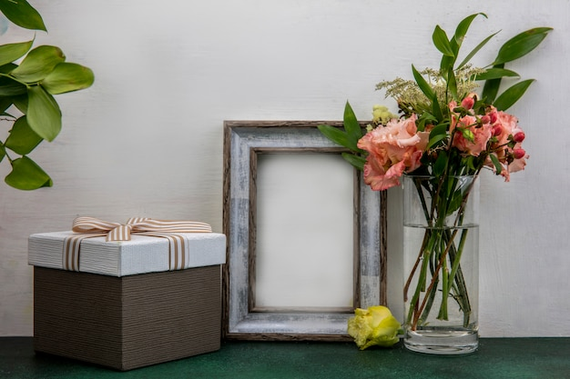 Zijaanzicht van mooie en verse bloemen met bladeren op een glas op witte ondergrond met kopie ruimte
