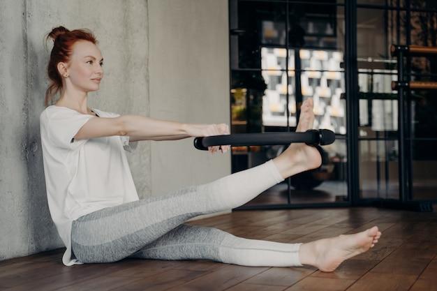 Zijaanzicht van mooie gemotiveerde fit vrouw zittend op de vloer in de fitnessstudio en het gebruik van zwarte pilates ring tijdens de training, fitness cirkel met beide armen en strekkende been in studio