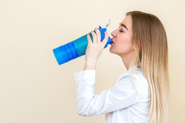 Zijaanzicht van mooie jonge blanke vrouw is drinkwater uit plastic fles
