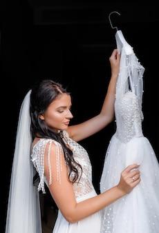 Zijaanzicht van mooie jonge bruid die een jurk in haar handen houdt op een zwarte geïsoleerde achtergrond
