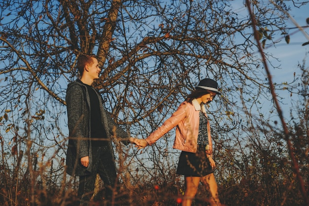 Zijaanzicht van mooie jonge vrouw en knappe man glimlachend en hand in hand tijdens het wandelen in de herfst platteland samen. vrolijk paar hand in hand en wandelen op het platteland
