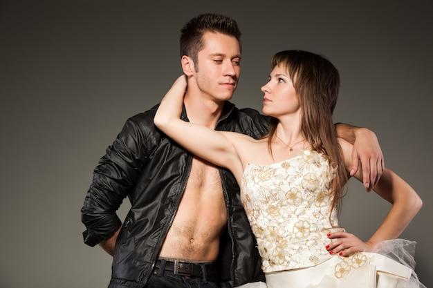 Zijaanzicht van mooie jonge vrouw man nek aan te raken en lichaam tegen vriendje te drukken.