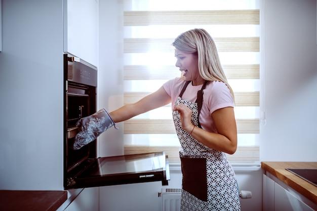 Zijaanzicht van mooie kaukasische blonde in schort die hete braadpan uit oven nemen. keuken interieur.