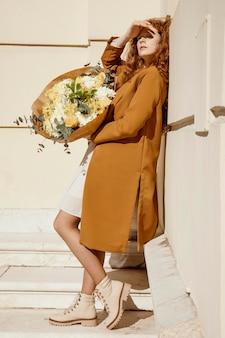 Zijaanzicht van mooie vrouw buitenshuis met boeket van lentebloemen