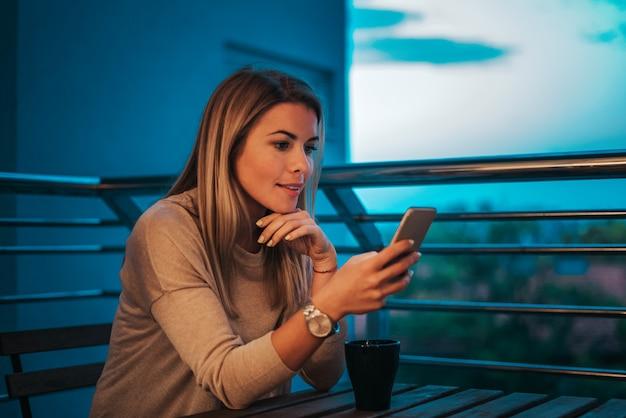 Zijaanzicht van mooie vrouw die smartphone gebruiken bij terras in de avond.