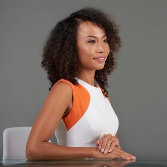Zijaanzicht van mooie vrouw in witte en oranje kledingszitting bij het bureau