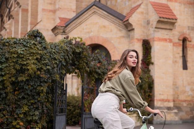 Zijaanzicht van mooie vrouw met fiets in de stad