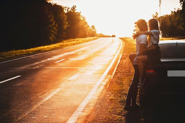 Zijaanzicht van mooie vrouw zittend op auto kofferbak hartstochtelijk omhelst man hand in hand rond haar middel op verlichte achtergrond van lege weg en bomen in de avond