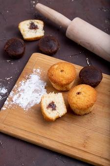 Zijaanzicht van muffins met chocolade op een houten snijplank