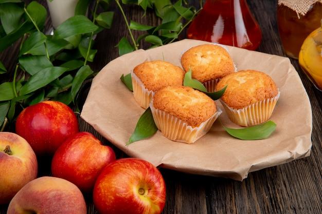 Zijaanzicht van muffins met groene bladeren op ambachtelijk pakpapier met verse rijpe nectarines op rustiek hout