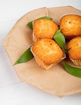 Zijaanzicht van muffins met groene bladeren op ambachtelijk pakpapier op wit rustiek hout