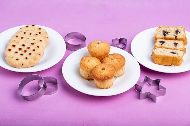 Zijaanzicht van muffins op een witte plaat en koekjessnijders op paars