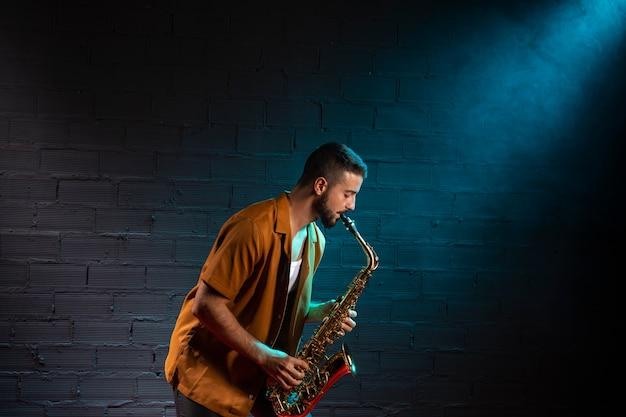 Zijaanzicht van musicus die de saxofoon in schijnwerpers speelt