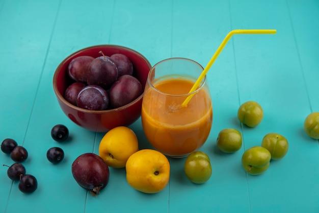 Zijaanzicht van nectacotsap met drinkbuis in glas en kom van pluots met nectacots pruimen en druiven bessen op blauwe achtergrond