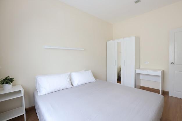 Zijaanzicht van nieuw modern wit houten bed in witte slaapkamer met zacht en duidelijk licht