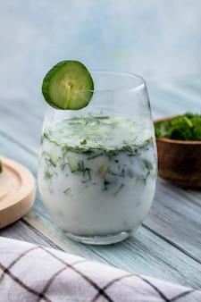 Zijaanzicht van okroshka in een glas met een komkommer en een witte geruite handdoek