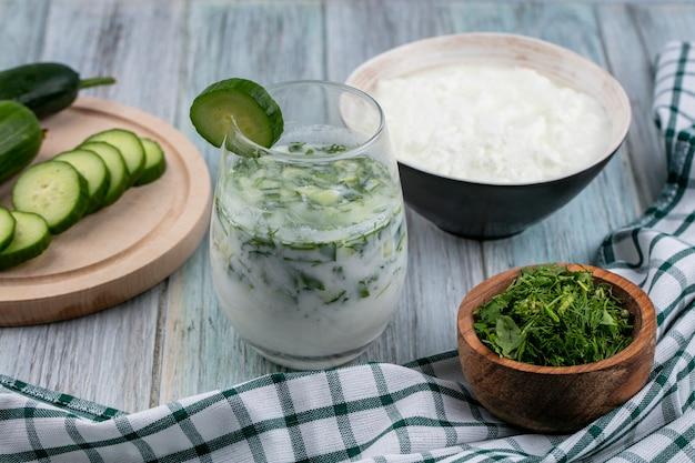 Zijaanzicht van okroshka in een glas met komkommers op een stand yoghurt en kruiden op een grijze ondergrond