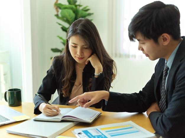 Zijaanzicht van ondernemers samen te werken aan hun project in moderne kantoorruimte